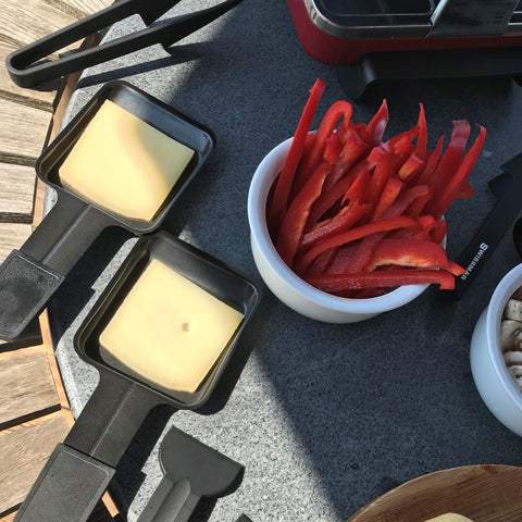 raclette cheese in dishes ready to melt under raclette grill
