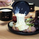 candle light melted raclette cheese poured over a plate