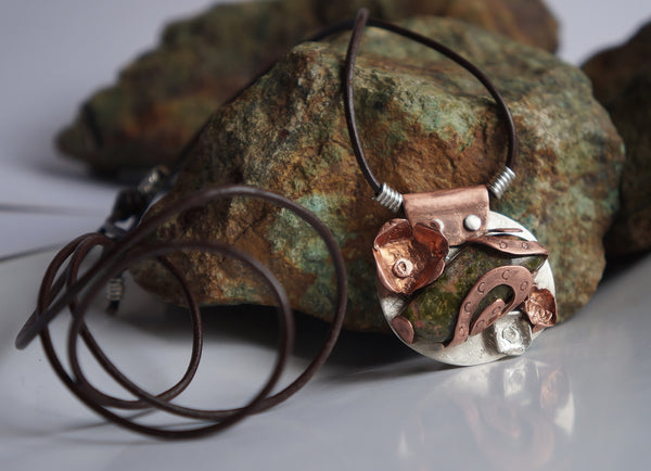 a copper, sterling silver, and unakite pendant with a leather necklace and turquoise rocks
