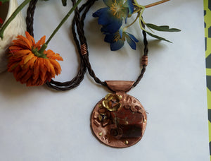 a western style copper and jasper pendant with a leather necklace and flowers