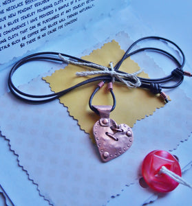 A handmade and riveted copper broken but mended heart pendant necklace