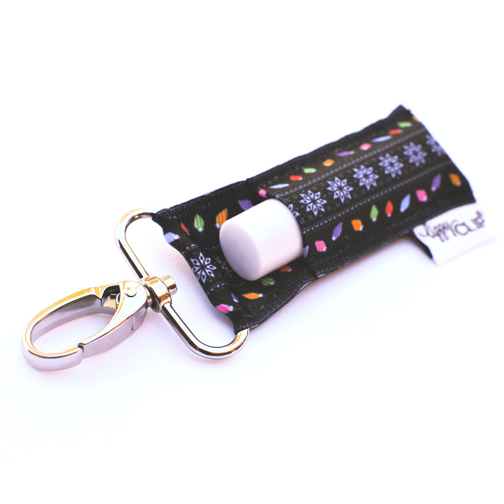 LippyClip Lip Balm Holder with silver clip, white background with snowflakes and Christmas lights