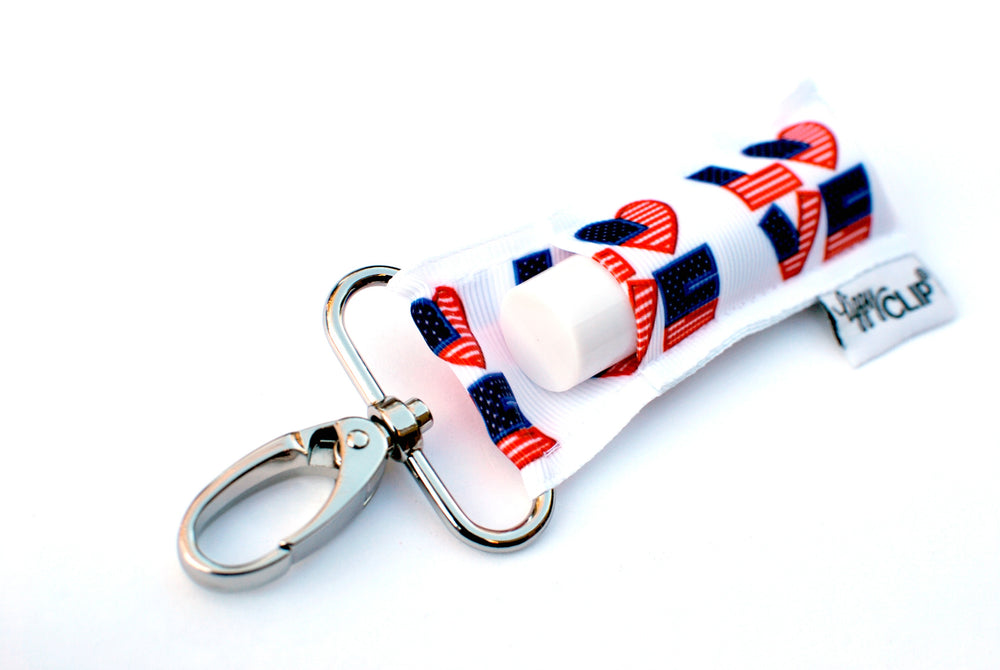 LippyClip Lip Balm Holder with silver clip, white background with American flag patterned L-O-V-E