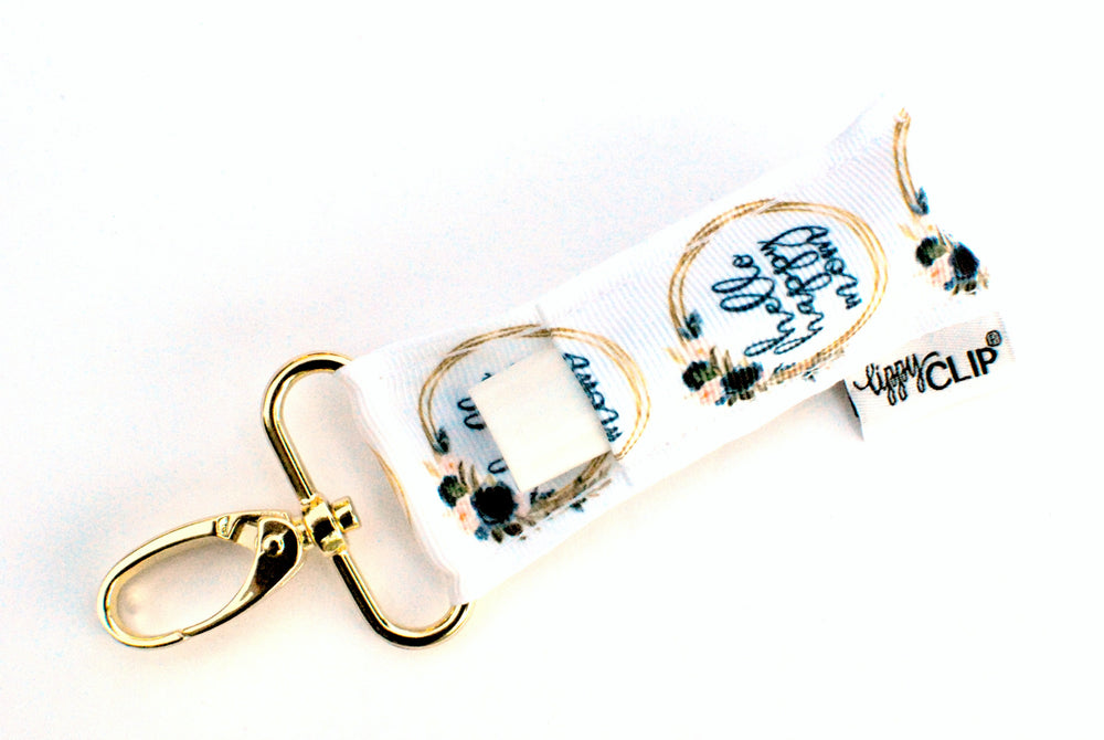 LippyClip Lip Balm Holder with gold clip, white background with Hello Happy Mom logo