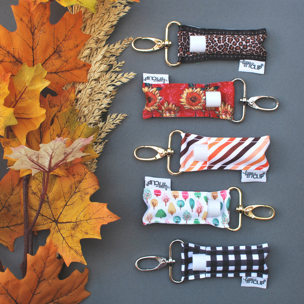 Fall LippyClip collection on grey background with flowers