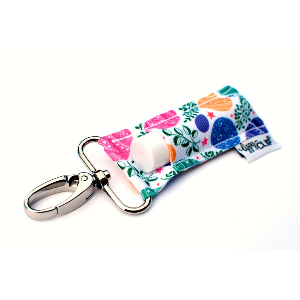 LippyClip Lip Balm Holder with silver clip, white background with painted Easter eggs and greenery