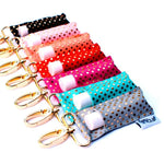 A row of seven LippyClips from the Gold Dots Collection. Colors include black, light pink, peach, red, hot pink, aqua, and grey.