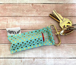 LippyClip Lip Balm Holder with gold clip, aqua background and gold polka dots clipped to key ring