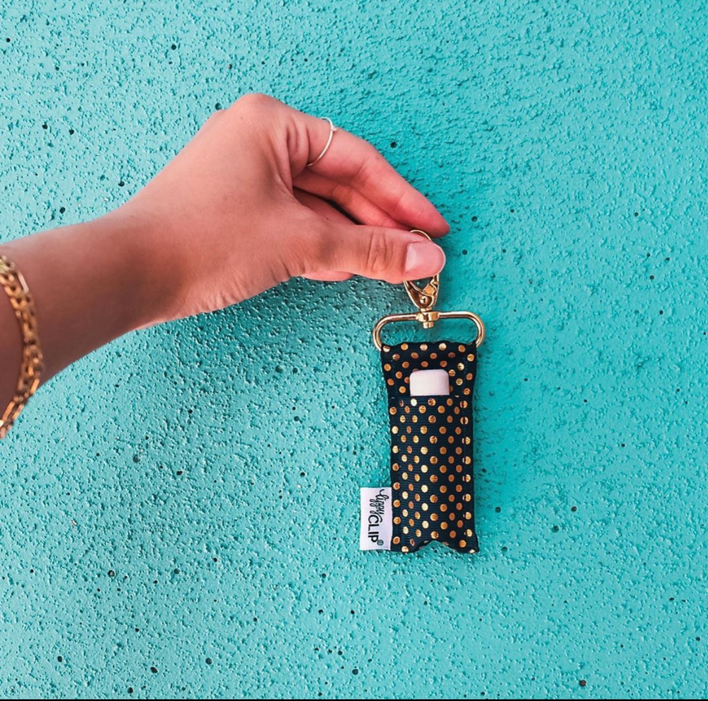 Woman's hand holding Black Gold Dots LippyClip against teal wall