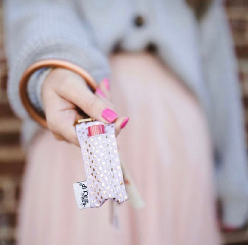 Woman holding pink purse with Light Pink Gold Dots LippyClip clipped to handle