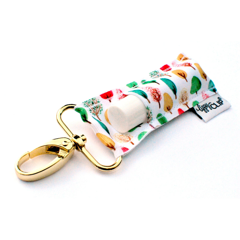 LippyClip Lip Balm Holder with gold clip, white background with green, red, and yellow trees