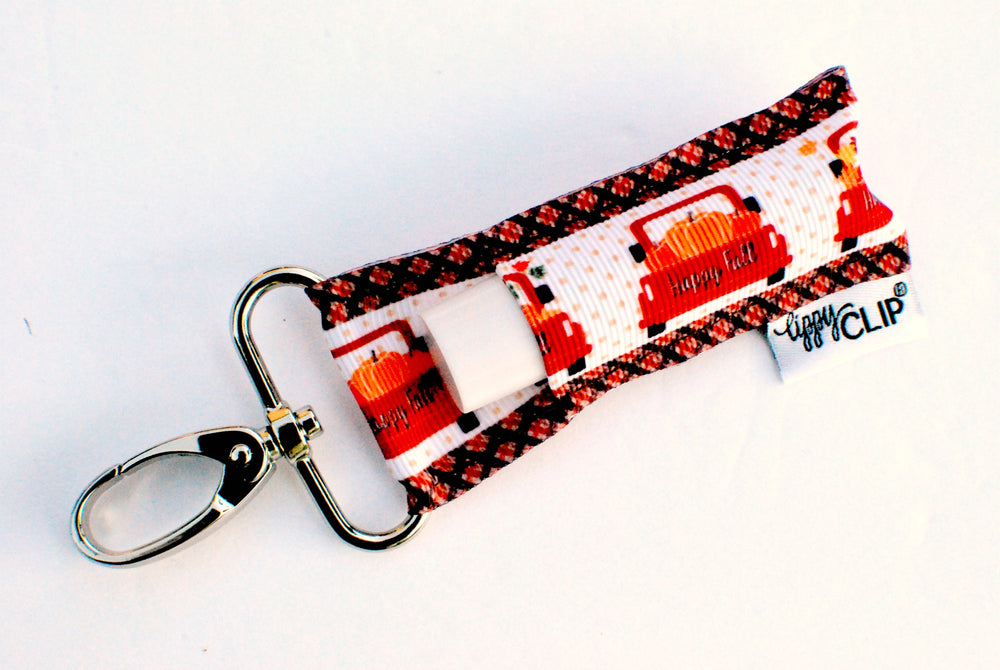 LippyClip Lip Balm Holder with silver clip, white background with black and orange plaid on the sides and cute orange trucks down the middle