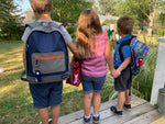 Three kids with backpacks with LippyClips clipped to zippers