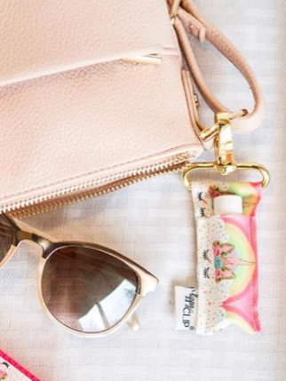 Rainbow Unicorn LippyClip clipped to purse with sunglasses