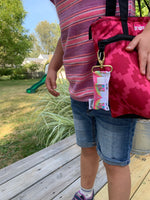 Girl holding tote bag with Rainbow Unicorn LippyClip clipped to zipper