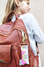 Rainbow Unicorn LippyClip clipped to girl's backpack