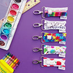 A collection of teacher and school themed LippyClips on a purple background with art supplies