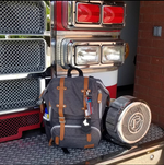 Thin Red Line LippyClip clipped to grey backpack on front of fire truck