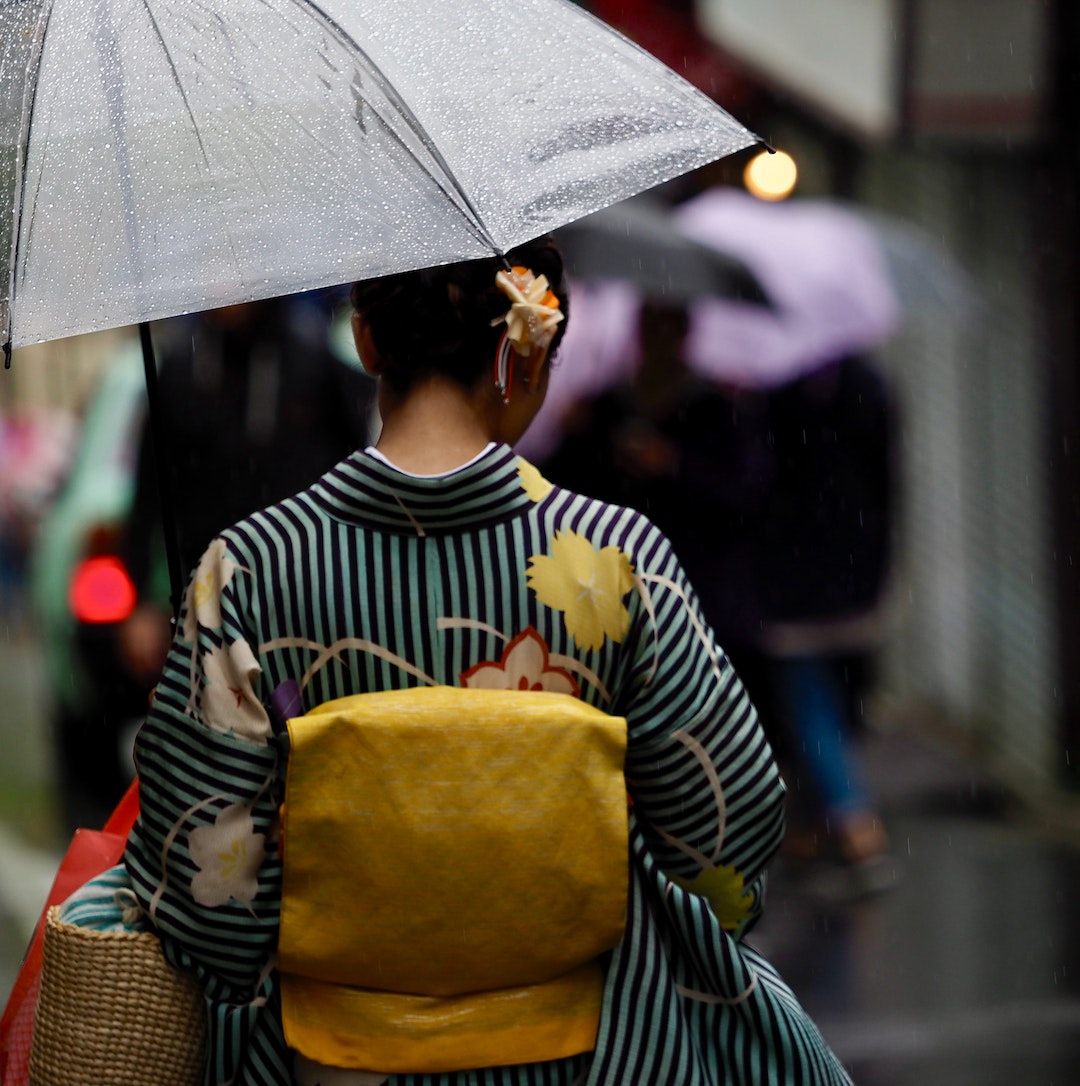 Woman wearing a kimono and carrying an umbrella. Photo by Adrien Bruneau on Unsplash.