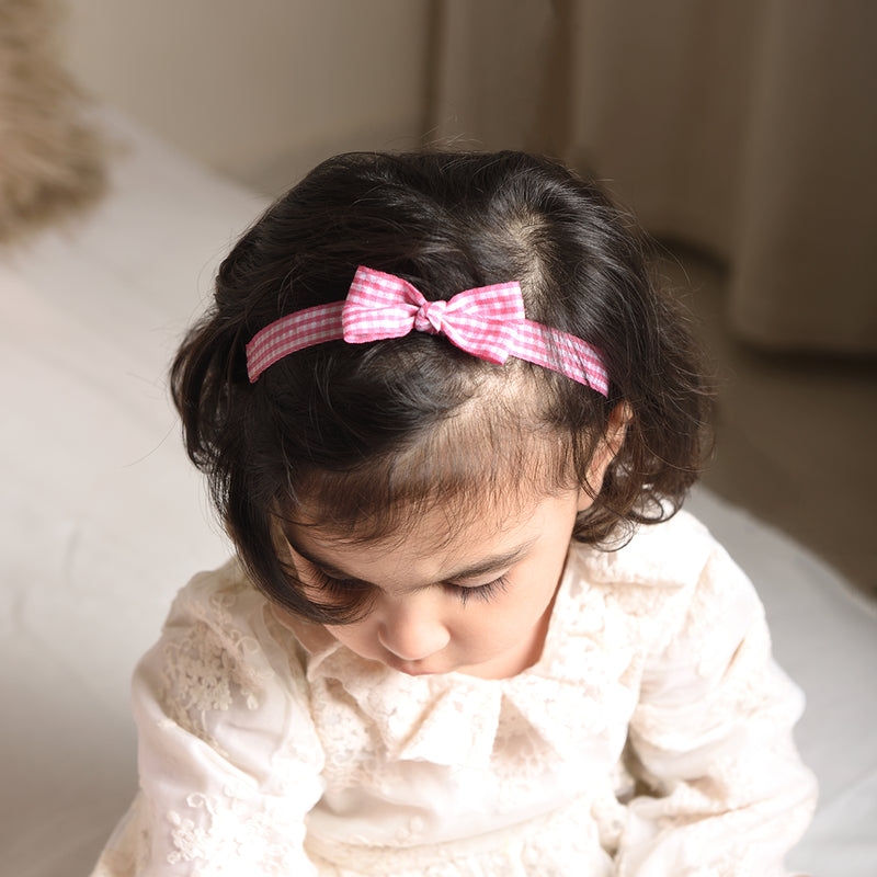A little girl wearing a white dress and a pink check headband with a bow on top. the girl is looking down.