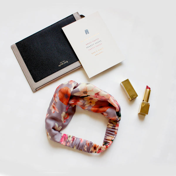 Flatlay of a grey floral elastic headband surrounded by boss girl accessories and quote.