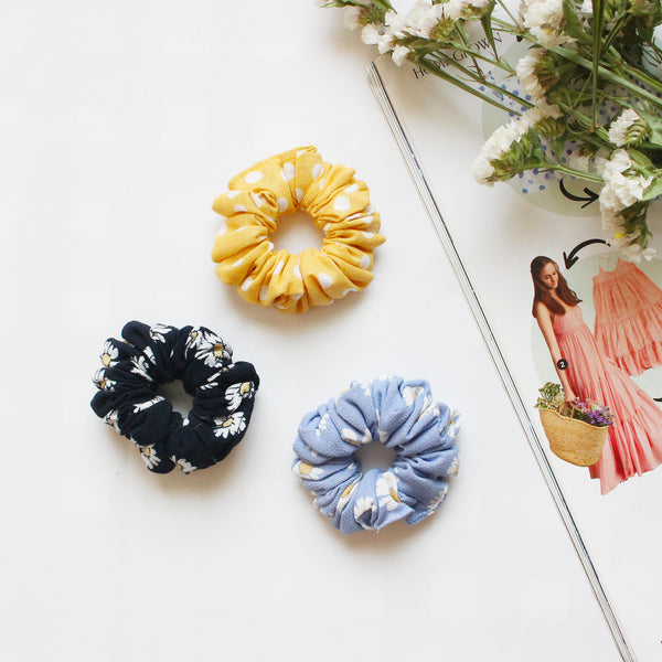 A flatlay of 3 scrunchies. One yellow polka dot, another black with white daisies on it, third blue with white daisies on it.