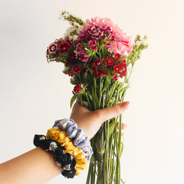 A hand holding a bouquet of red flowers with three scrunchies on the wrist.