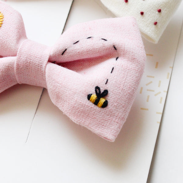 A close up of a pink bow with a honey bee embroidered on it.