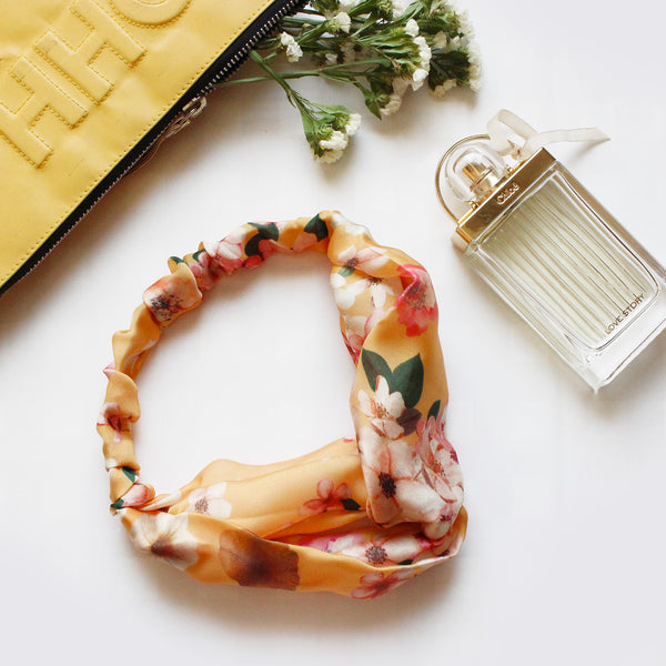 Flatlay of a yellow floral elastic headband placed alongside a perfume bottom and some flowers.