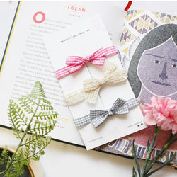 Three headbands for babies on a white card. Kept on a book talking about Lozen the warrior. one pink check headband with a bow on top. one off white lace headband with a knotted bow and one light grey check headband with a bow on top. surrounded by little flowers and ferns on the sides