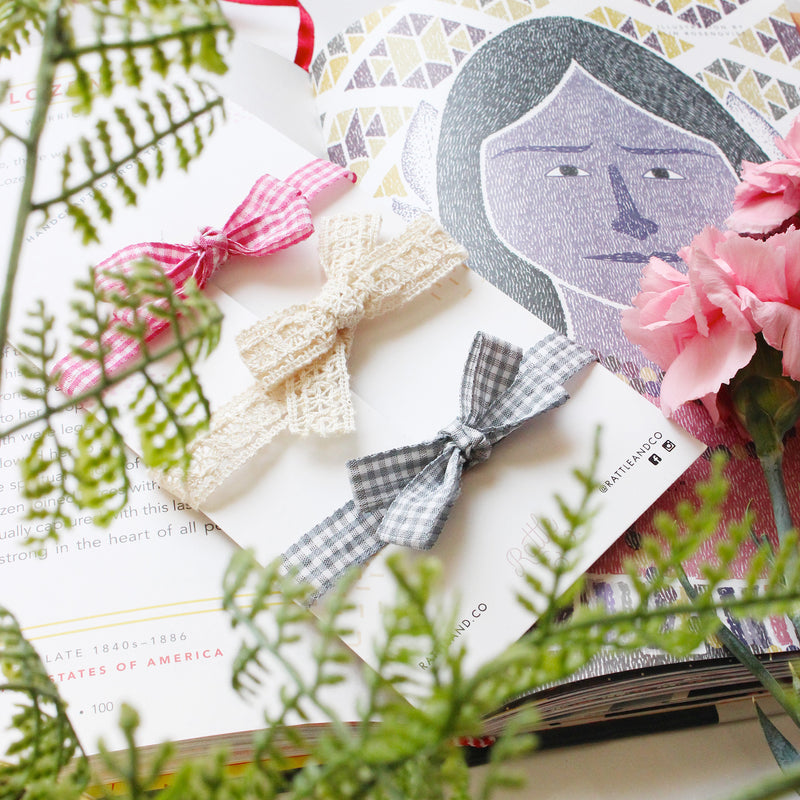 Three baby nylon headbands on a white card kept on a book and surrounded by flowers.