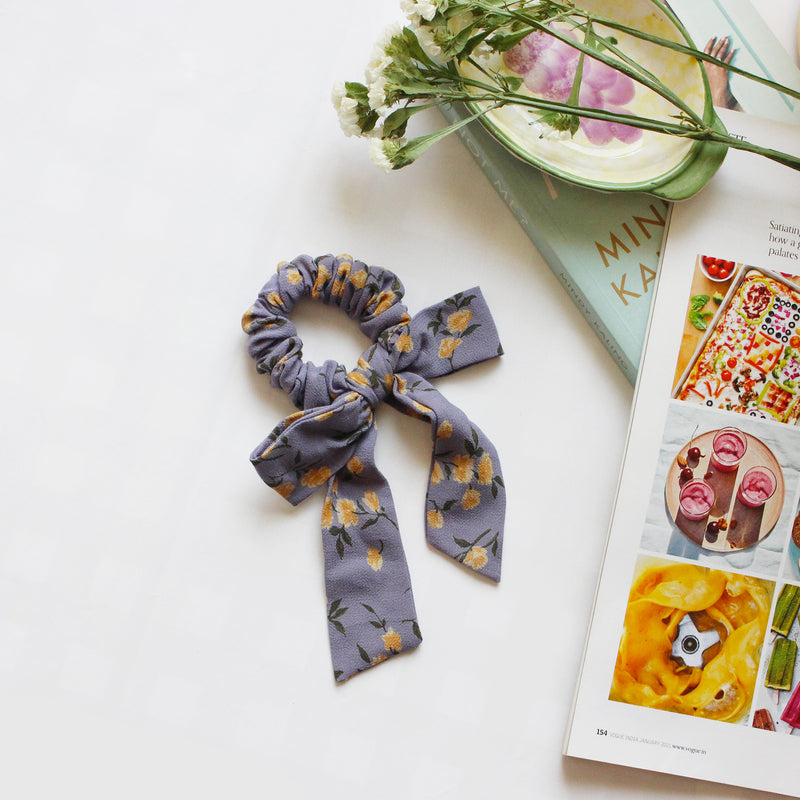 A mauve colored scrunchie with yellow flowers printed on it. A long tailed bow is tied to the scrunchie in the same fabric.