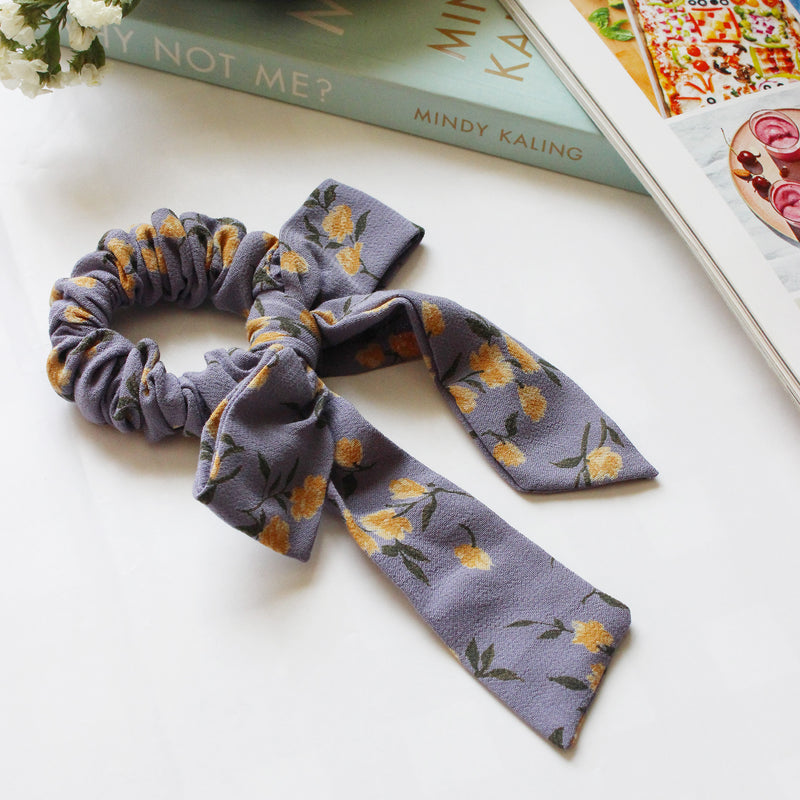 A scrunchie with a long -tailed bow in a blue floral printed fabric. Yellow flowers spead across the scrunchie.