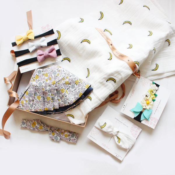 a new born baby gift box consisting of a swaddle, a bib, 3 mini bow headbands and one flower crown