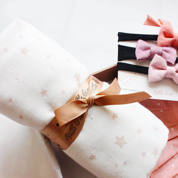 a close up of a white muslin swaddle with little stars printed across it tied with a ribbon