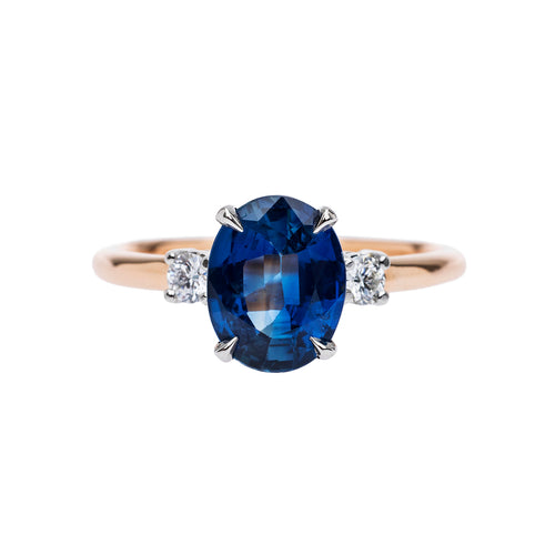 Oval Ceylon Sapphire flanked by two accent diamonds, rose gold and platinum