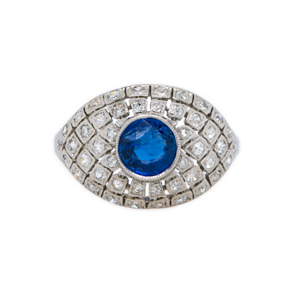 Luxumberg is a Belle Epoch era bombe style platinum and diamond ring featuring a .97ct Burmese sapphire, circa 1912 to 1926