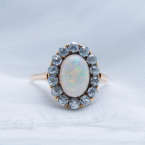 Seagrove | A beautiful and authentic Victorian era oval opal and diamond halo ring in 14k rose gold