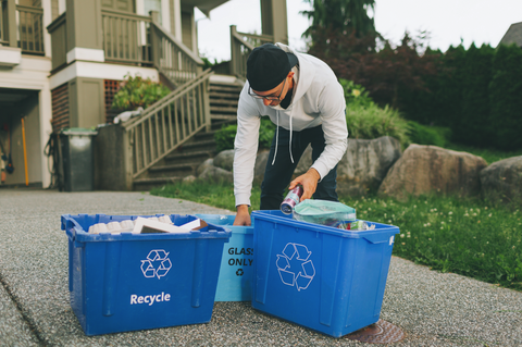 man organizes things into recycling bins