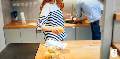 Woman holds a fruit while standing at a kitchen counter