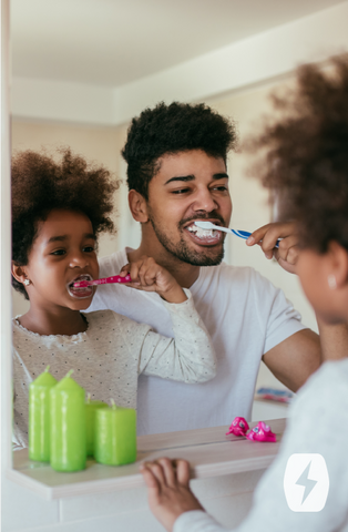 A father and daughter brush their teeth