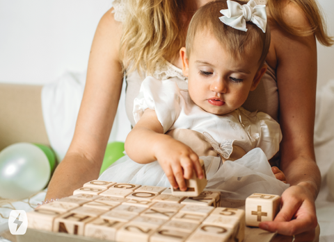 A mother holds a child as she plays with wooden blocks
