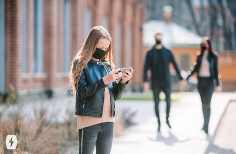 A girl wears a mask while she uses her phone