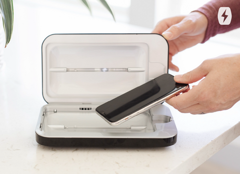 A phone being put into a PhoneSoap UV sanitizer