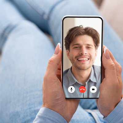 Hands hold a phone that is video calling a man