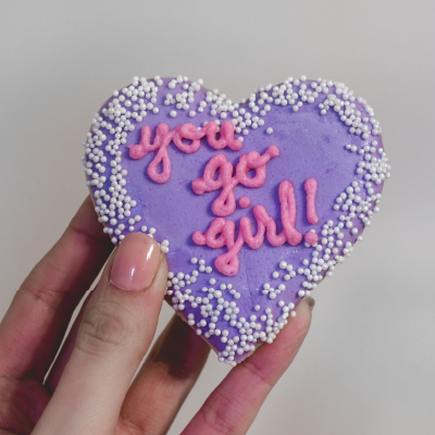 "Purple heart-shaped cookie with the words ""You Go Girl"" iced on it"