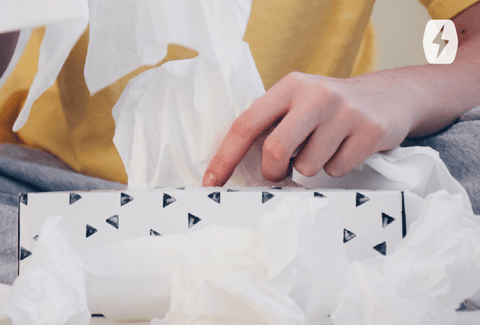 Hands pulling tissues out of a box
