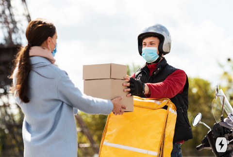 A woman wearing a mask grabs a box from a mask-wearing man