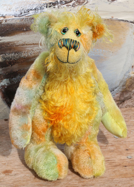 Alexander Appleshine is a sweet and gently colourful one of a kind, artist bear in gorgeous hand dyed mohair by Barbara-Ann Bears, he stands 11.5 inches( 29cm) tall and is 9 inches ( 23 cm) sitting. He's mostly made from a short, straight pile mohair hand dyed in shades of lime, jade, deep peach and lilac.