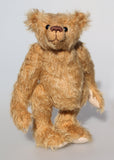 Benji is a sweet and charming, traditional one of a kind mohair artist bear by Barbara Ann Bears, he stands 9.5 inches/24 cm tall and is 7 inches/18 cm sitting. Benji is made from a slightly distressed, antique gold German mohair with beige wool-felt paw pads and vintage boot buttons for eyes